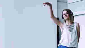 Man sieht ein Bild von Kristina, wie sie während dem Tanzen ihre Hand oben hält und die Augen zu hat. Sie hat Kopfhörer auf und genießt offensichtlich die Musik.