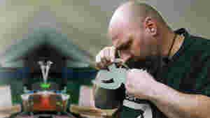 Stephan steht auf diesem Bild in der rechten Bildhälfte. Er befindet sich in seinem Atelier und man kann im Hintergrund seinen Werktisch mit allerhand Materialien erkennen. In den Händen hält er eine kleine Nagelschere, mit welcher er aus weißem Papier eine menschenähnliche Gestalt ausschneidet. Dabei geht er mit dem Kopf ganz nah an das Papier heran um die Umrisse der Form besser wahrnehmen zu können.  Auf seiner Stirn sind konzentrierte Falten zu sehen.