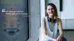 """Man sieht Kristina von vorne im Portrait. Sie sitzt und lächelt in die Kamera. Links steht ein Zitat von ihr: """"Ich bewege mich zu allem, was mich bewegt."""""""