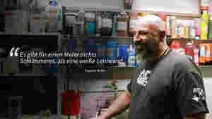 """Man sieht ein Portrait von Stephan Müller von der Seite, wie er vor seiner Sammlung von Acrylfarben steht. Er steht auf der rechten Seite des Bildes und schaut nach links. Links steht im Text als Zitat von Stephan Müller: """"Es gibt für einen Maler nichts Schlimmeres, als eine weiße Leinwand."""""""
