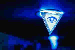 Ein Auge ist auf einem weißen Fahnenwimpel vor einer Lampe. Der Raum ist in blau beleuchtet.