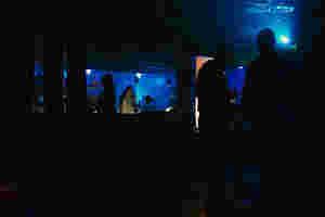 Der Raum ist abgedunkelt, nur der Barkeeper scheint hell erleuchtet zu sein. Zu rechten Seite reden zwei Männer.