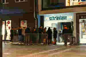 Direkt vor dem Eingang der Schräglage. Menschen warten auf den Einlass während sie zahlen und kontrolliert werden. Der Eingang ist durch Metallzäune abgetrennt.