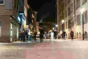 Vor der Schräglage stehen Menschen. Passanten laufen vorbei. Die Straße ist in einem gelben Licht erleuchtet.