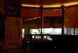 """Auf der linken Seite ist der Bier-Automat zu sehen. Darüber steht auf einem schwarzen Schild in großen Buchstaben """"Beer 0,5 L"""". Es sind Pfeile daran gezeichnet. Auf der rechten Seite sind Sitzmöglichkeiten."""