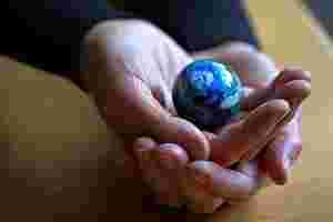 Zu sehen ist eine Erde in Miniaturform, die von zwei Händen gehalten wird.
