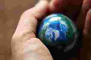 Zu sehen ist eine Erde in Miniaturform, die von einer Hand gehalten wird.