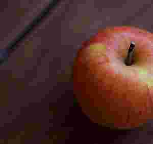Zu sehen ist ein rötlicher Apfel.